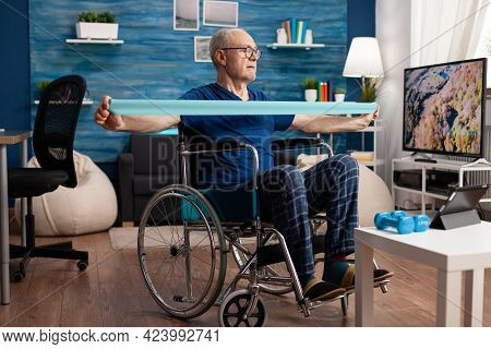 Disabled Senior Man In Wheelchair Training With Elastic Band Exercising Body Workout Recovering Afte