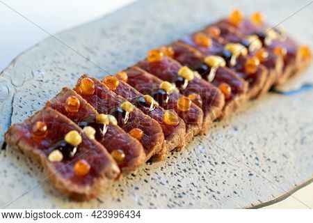 Macro Close Up Of Appetizing Wagyu Beef Sirloin Tataki. Multiple Slices Of Crisp And Reddish Meat Or