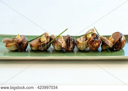 Close Up Front View Of Grilled Porcini Mushrooms With Crisp Pork Strips And Garlic Mayonnaise.