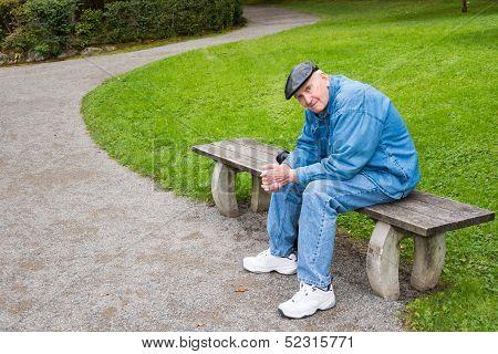 Elderly Man Sitting On Park Bench