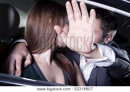 Young couple kissing in car and man is shielding with his arm