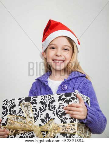 Portrait of happy girl in Santa hat holding Christmas gift at home