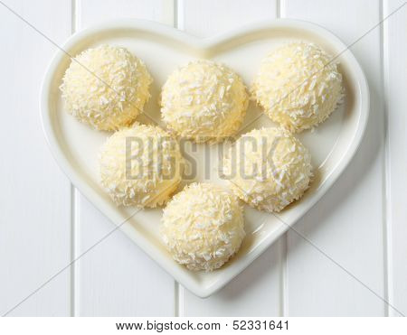white chocolate pralines with grated coconut on a heartshaped plate