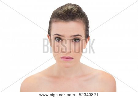 Puzzled natural brown haired model looking at camera on white background