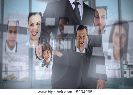Classy businessman presenting profile pictures on digital interface