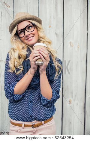 Happy fashionable blonde holding coffee outdoors on wooden background