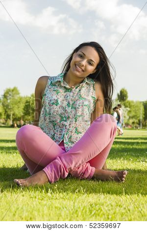Outdoor portrait of a beautiful African American woman sitting onn the grass