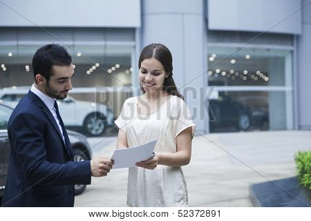 Car salesman and young woman looking over paperwork