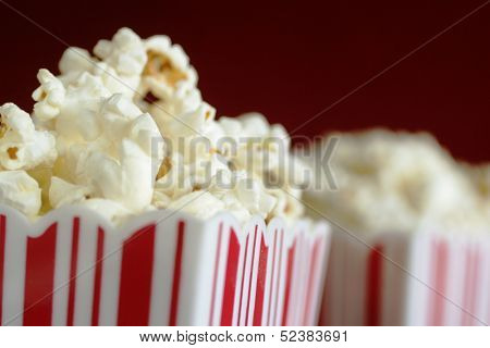 Close up of a container full of pop corn with a second one in background