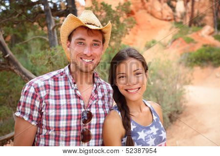 Happy outdoors couple portrait in american countryside. Smiling multiracial young couple in western USA nature. Man wearing cowboy hat and woman wearing USA flag shirt.