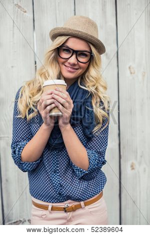 Happy trendy blonde holding coffee outdoors on wooden background