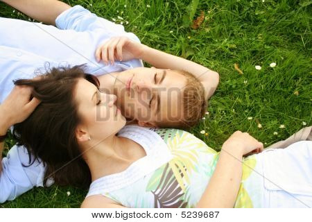 Couple Is Cuddle On A Green Meadow