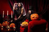 Halloween concept: sexy ladies vampire with halloween pumpkins over red background poster