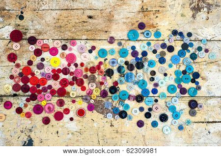 Sewing buttons on grunge wood background