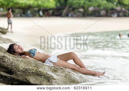 Filipina woman lying on rocky beach