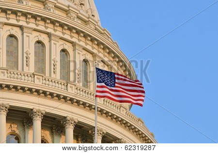 The U.S. Capitol building dome detail and waving American flag - Washington DC