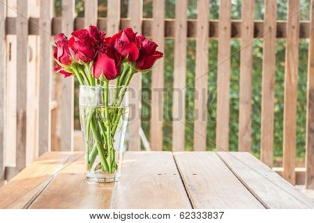 Group Of Red Roses On Wooden Table