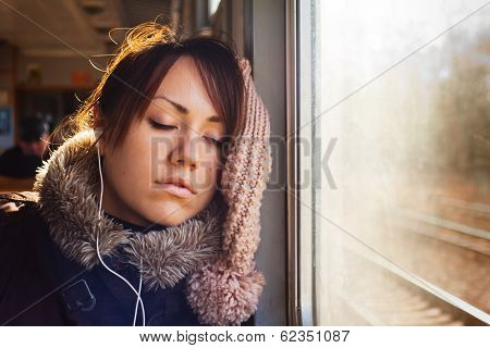 The sleeping girl with headphones in train