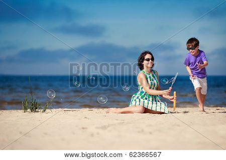 Young mother making soap bubbles with his child
