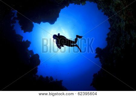 Scuba Diver swims over underwater cave, silhouette against sun