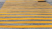Pedestrian crossing road marking with yellow stripes on asphalt poster