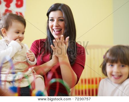 Two Little Girls And Female Teacher In Kindergarten