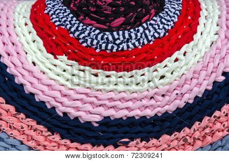 Knitted colorful rustic rug of bright woolen bands poster