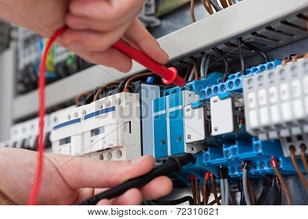 Electrician Examining Fusebox With Multimeter Probe