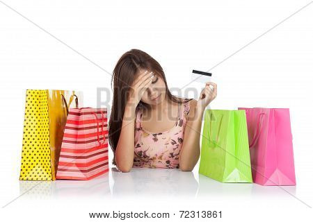 Beautiful Asian Woman Fed Up With A Credit Card And Shopping Bags On Table
