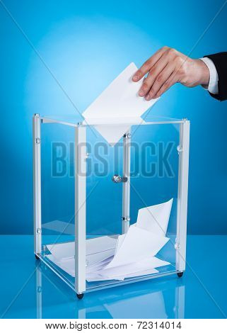 Businessman Putting Paper In Polling Box