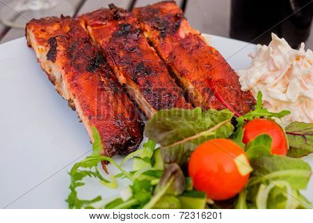 Ribs With Some Salad And Coleslaw In The Corner