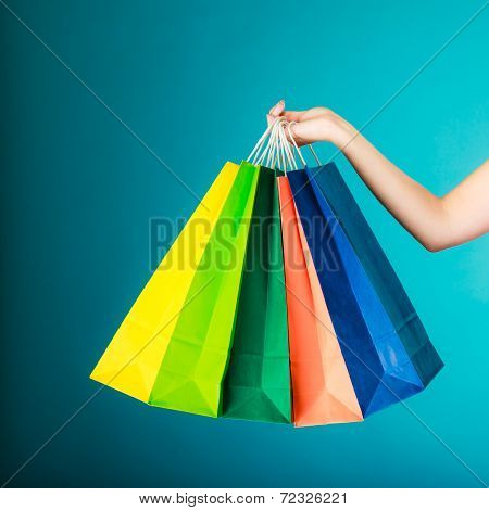 Closeup of colorful paper shopping bags in female hand on vibrant blue. Woman girl buying clothes. Sale and retail. poster