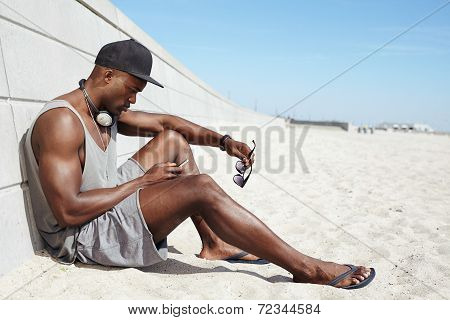 Young African Guy Sending A Text Message At The Beach