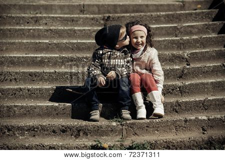 litle boy kissing girl
