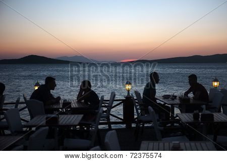 People sit in outdoor restaurant at dusk