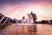 Sunset view of Patuxai arch or Victory Triumph Gate monument with fountain in front. Vientiane Laos travel landscape and destinations poster