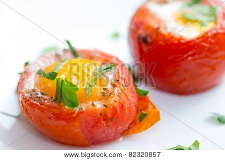 Baked, de-seeded tomatoes filled with an egg and finished in the oven, served on toast with a parsley garnish. This Italian dish is uova al piatto con pomodori poster