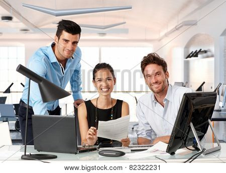 Happy team of young business people working together in office.