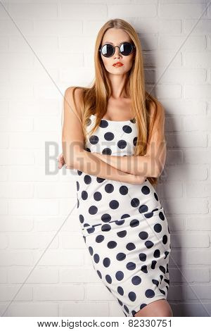 Fashionable lady in polka-dot dress posing near white brick wall. Beauty, fashion concept. Optics.