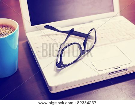 Cup of coffee and laptop with a pair of hipster glasses on wooden table toned with a retro vintage instagram filter