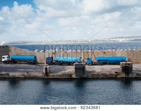 Tankers lined up on a cement wharf or dock on a pier at the side of a harbor waiting to refuel a ship or offload cargo