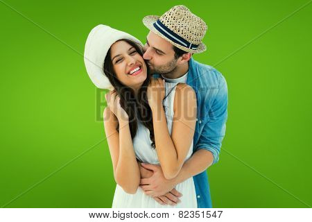 Happy hipster couple hugging and smiling against green vignette