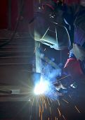 welder working with electrode at semi-automatic arc welding in manufacture production plant poster