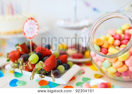 Cake, candies, marshmallows, cakepops, fruits and other sweets on dessert table at kids birthday party