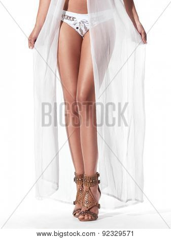 Sexy woman in white sheer beachwear robe and bikini closeup of legs in sandals isolated on white background