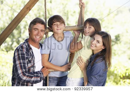 Family In Garden By Treehouse