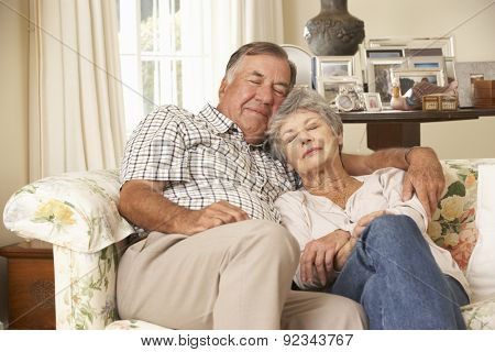 Retired Senior Couple Dozing On Sofa At Home Together