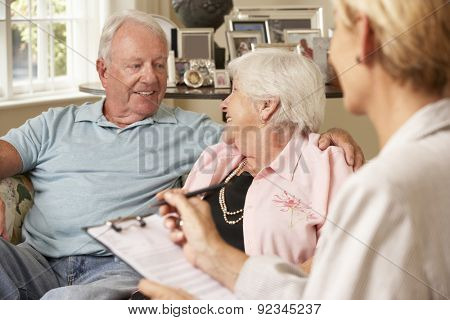 Retired Senior Couple Sitting On Sofa Talking To Financial Advisor