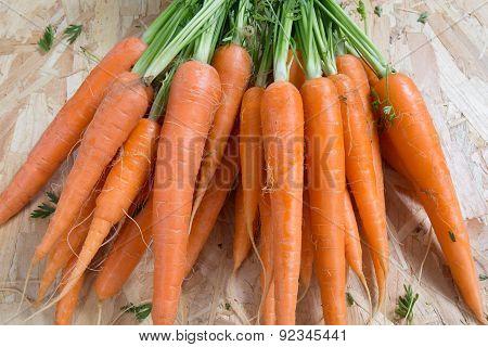 Harvest Of Organics Carrotts On A Wood Table.