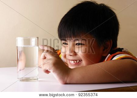 Kid touching a glass of water on a wooden table